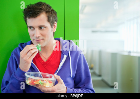 Businessman eating gum drops - Stock Photo