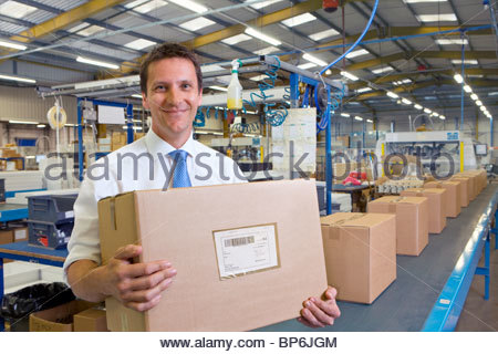 Worker in warehouse on assembly line holding cardboard box - Stock Photo