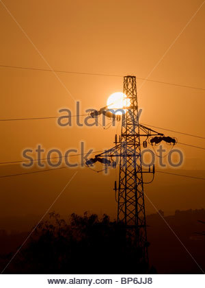 Electricity pylon silhouetted against sky at sunset, Sicily, Italy - Stock Photo