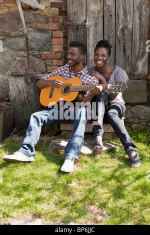 A man playing an acoustic guitar with his girlfriend - Stock Photo