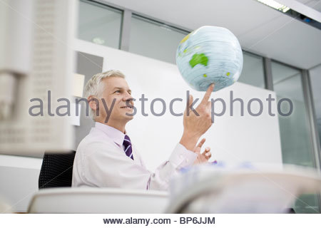 A businessman sitting at a desk spinning an inflatable globe on his finger - Stock Photo