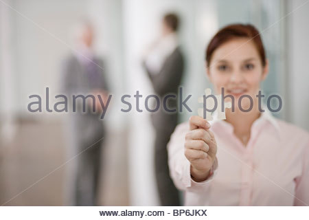 A businesswoman holding a piece of a jigsaw, two businessmen in the background - Stock Photo