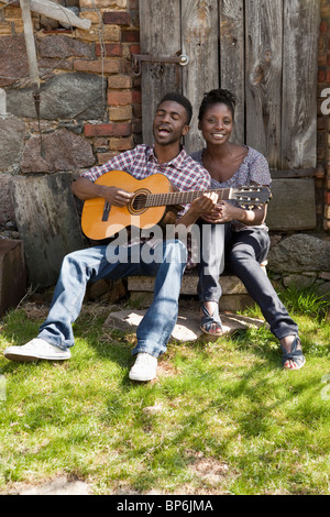 A man playing an acoustic guitar and singing with his girlfriend - Stock Photo