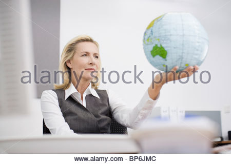 A businesswoman in an office holding a globe - Stock Photo