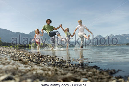 A family paddling in a lake, kicking the water - Stock Photo