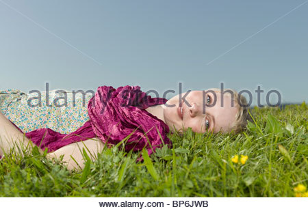 A young woman lying in the grass wearing a magenta scarf - Stock Photo