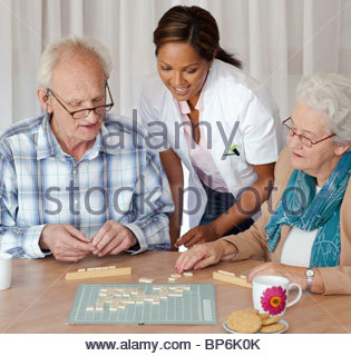 A senior couple and care assistant playing a board game together - Stock Photo