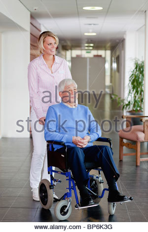 Smiling carer pushing an old man in a wheelchair stock photo image - A Care Assistant Pushing A Senior Man In A Wheelchair With