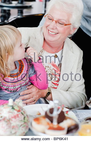 A little girl sitting on her grandmothers knee eating cake - Stock Photo