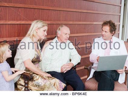 An elderly man and his family talking to a medical consultant - Stock Photo