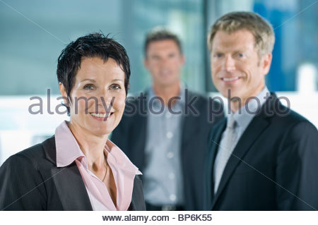 A businesswoman with two male colleagues in the background - Stock Photo