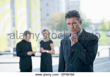 A businessman looking thoughtful, two businesspeople in the background - Stock Photo
