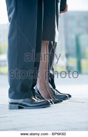 Two businessmen and a businesswoman standing in a row, close-up of their legs - Stock Photo