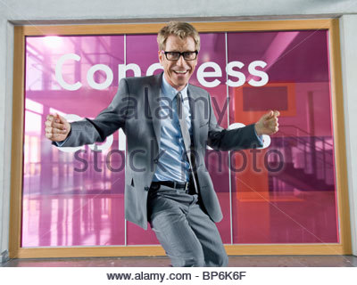 A mature businessman dancing in front of a congress centre - Stock Photo