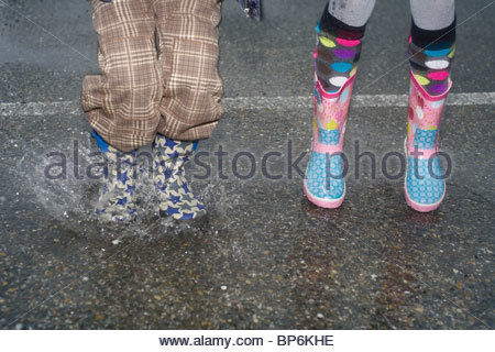 Young children jumping in a puddle wearing Wellington boots - Stock Photo