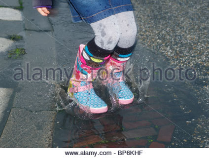A young girl jumping in a puddle wearing Wellington boots - Stock Photo