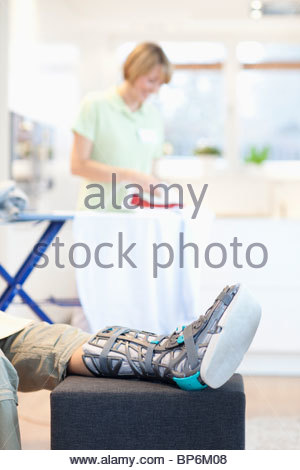 Man with foot brace relaxing at home, woman in background ironing - Stock Photo