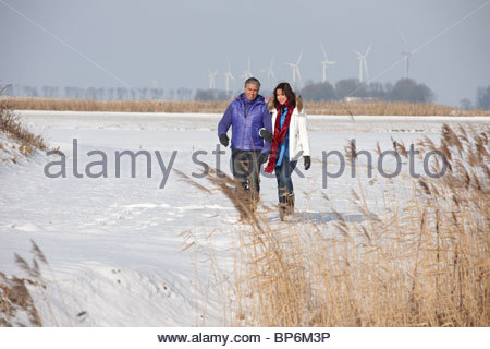 Mature couple walking through snow in Flevoland, The Netherlands - Stock Photo