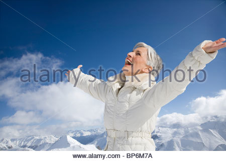 Mature woman with arms wide open on winter day - Stock Photo