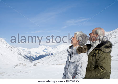 Senior couple enjoying the mountain view on winter day - Stock Photo