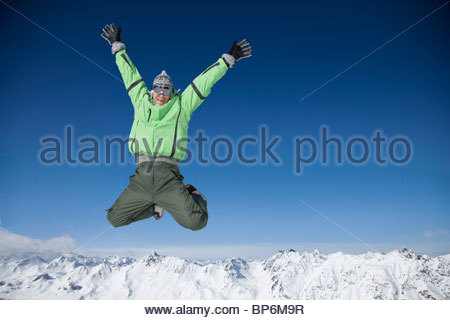 Mid adult man in ski gear jumping in midair - Stock Photo