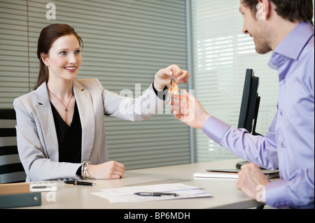Female real estate agent giving house keys to a man - Stock Photo