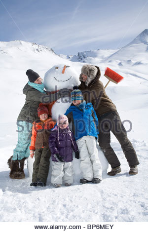 Portrait of young family with snowman on winter day - Stock Photo