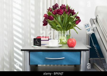 Various objects on a bedside table in a hospital ward - Stock Photo