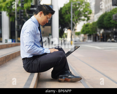A businessman sitting cross-legged on some steps, using a laptop - Stock Photo
