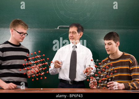 A teacher showing students molecular structure models - Stock Photo