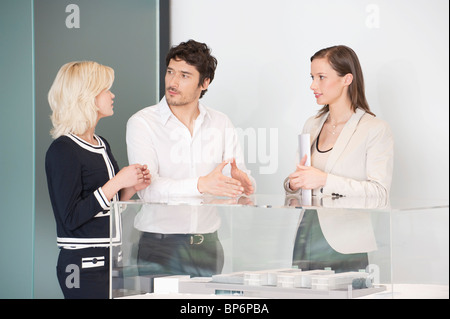 Man with two women near an architectural model - Stock Photo