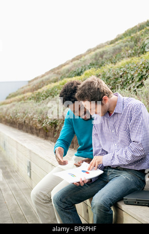 Friends discussing documents on a boardwalk