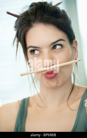 Woman balancing a pencil on lip - Stock Photo