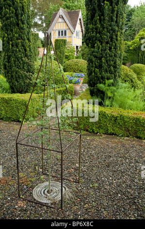 Young Tree with Topiary metal structure, box hedging and garden folly in the background.  Bryans Ground, UK. - Stock Photo