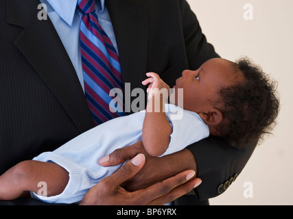 Businessman holding baby - Stock Photo
