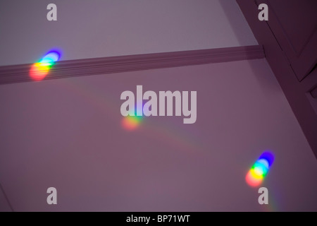 A colour (color) spectrum of visible light shines onto bedroom wall sourced from a window-situated prism. - Stock Photo