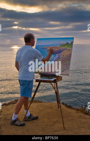 Artist Bill Jewell plein aire painting on coastal bluff overlooking the ocean at Sunset Cliffs, San Diego, California - Stock Photo