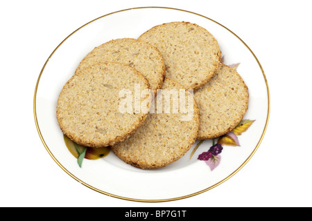 Stack of sunflower and pumpkin seed oatcakes on a white plate - Stock Photo