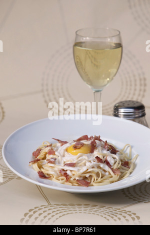 plate of linguine with bacon and fried egg and glass of white wine - Stock Photo