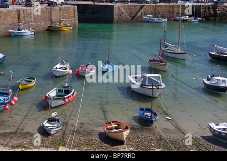 Fishing Boats moored in Mousehole harbour. Colourful fishing and small pleasure craft moored to the beach shore - Stock Photo