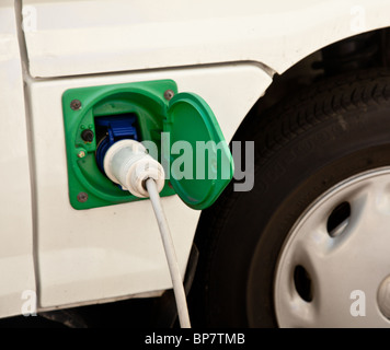 Electric car charging point of a new hybrid electric car being recharged with electricity - Stock Photo
