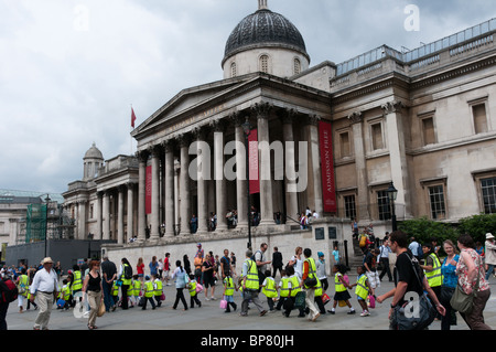 A group of school children on an outing cross Trafalgar Square in London wearing high-vis jackets - Stock Photo