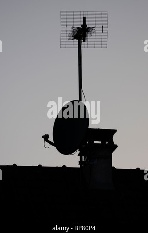 A silhouette of s Sky satellite dish and terrestrial aerial mounted on a house. - Stock Photo