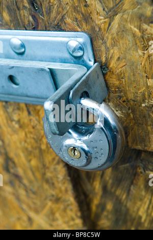 Door locked with padlock - Stock Photo