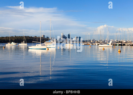 Yachts moored at Matilda Bay on the Swan River, with Perth's skyscrapers in the distance. - Stock Photo