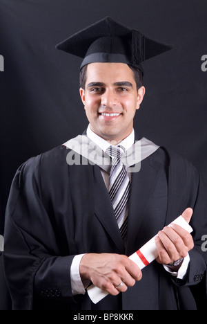 Young university graduate in graduation cap and gown holding diploma - Stock Photo