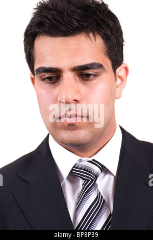 Portrait of a serious young Middle Eastern business man looking down cutout against a white background - Stock Photo