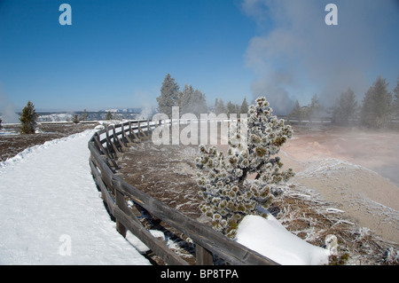 USA, Wyoming. Yellowstone National Park. Fountain Paint Pot trail in winter. Snow covered trail next to hot mud - Stock Photo