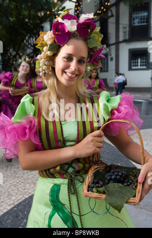 Young woman in colourful costume at the Madeira Wine Festival, Funchal, Madeira, Portugal - Stock Photo
