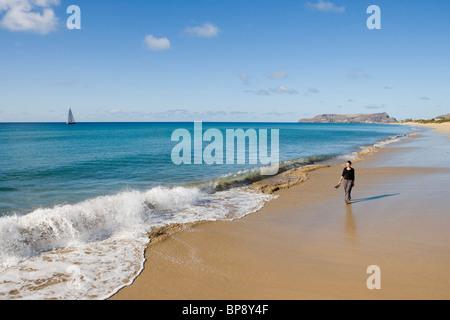Woman strolling along Porto Santo Beach, Porto Santo, near Madeira, Portugal - Stock Photo